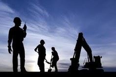 Silhouette of construction workers in field