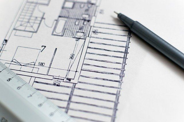 drawings of a construction project with a pen